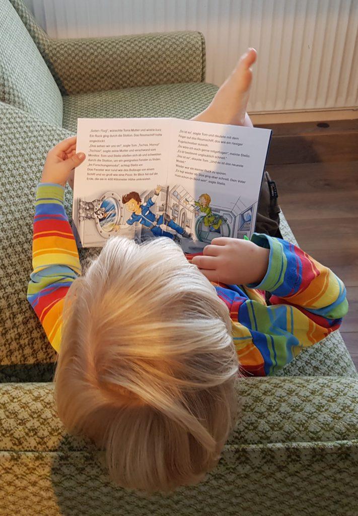 Selbstlesen. Junge liegt auf dem Sofa und liest